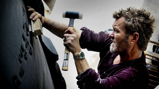 Magne at Tommerup Ceramic Workshop, hammering letters into one of the massive jars (Picture from Aftenposten)